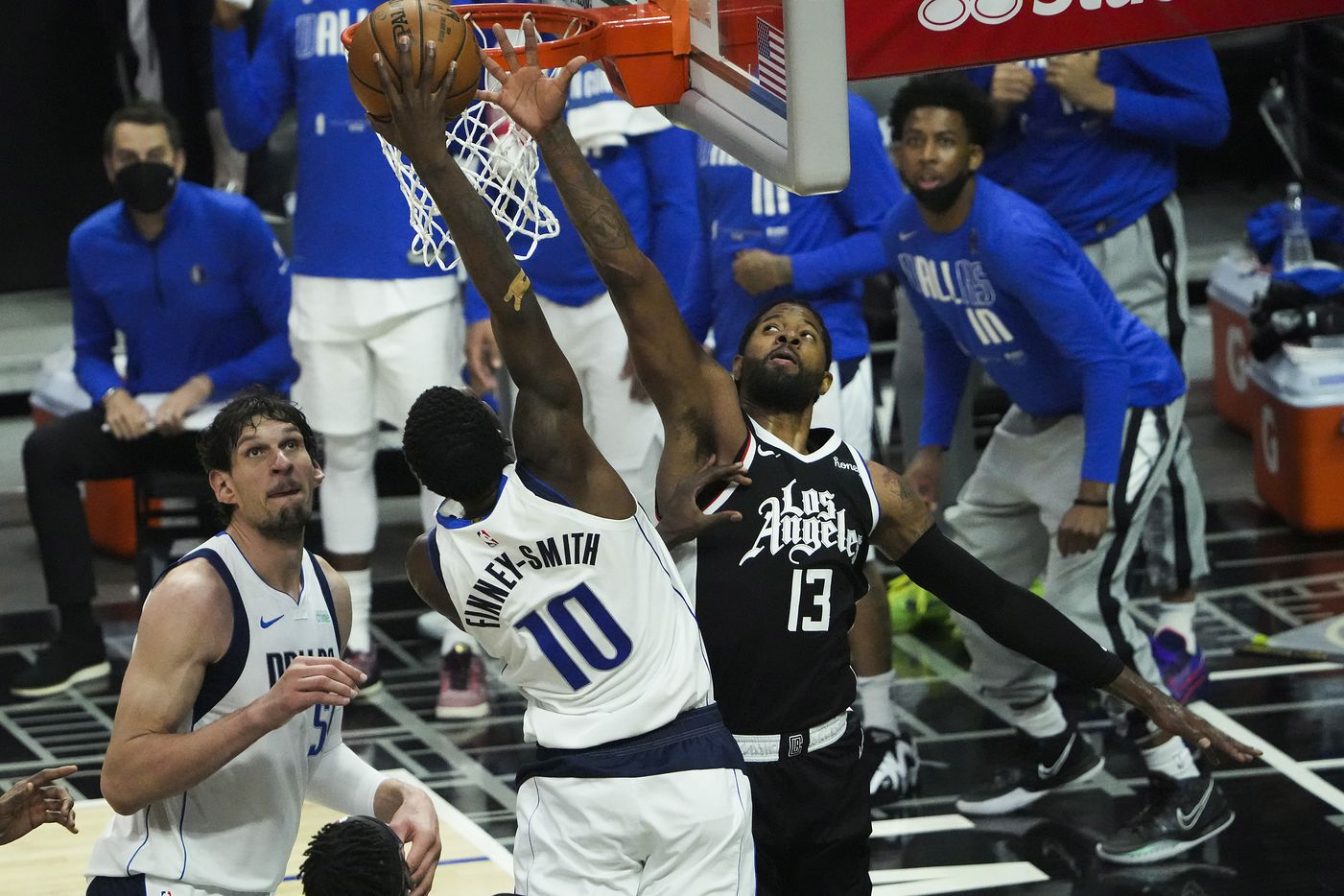 Dallas Mavericks forward Dorian Finney-Smith (10) dunks the ball past LA Clippers guard Paul George (13) during the second quarter of Game 7 of an NBA playoff series at the Staples Center on Sunday, June 6, 2021, in Los Angeles.