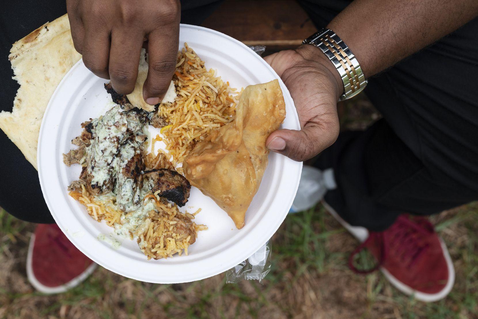 Abdelhalim Awadalla, 28, eats from a plate of Chicken Biryani, Samosa, and Seekh Kebab, during a PunjabiTex BBQ popup, conducted by Chef Usama Khalid.