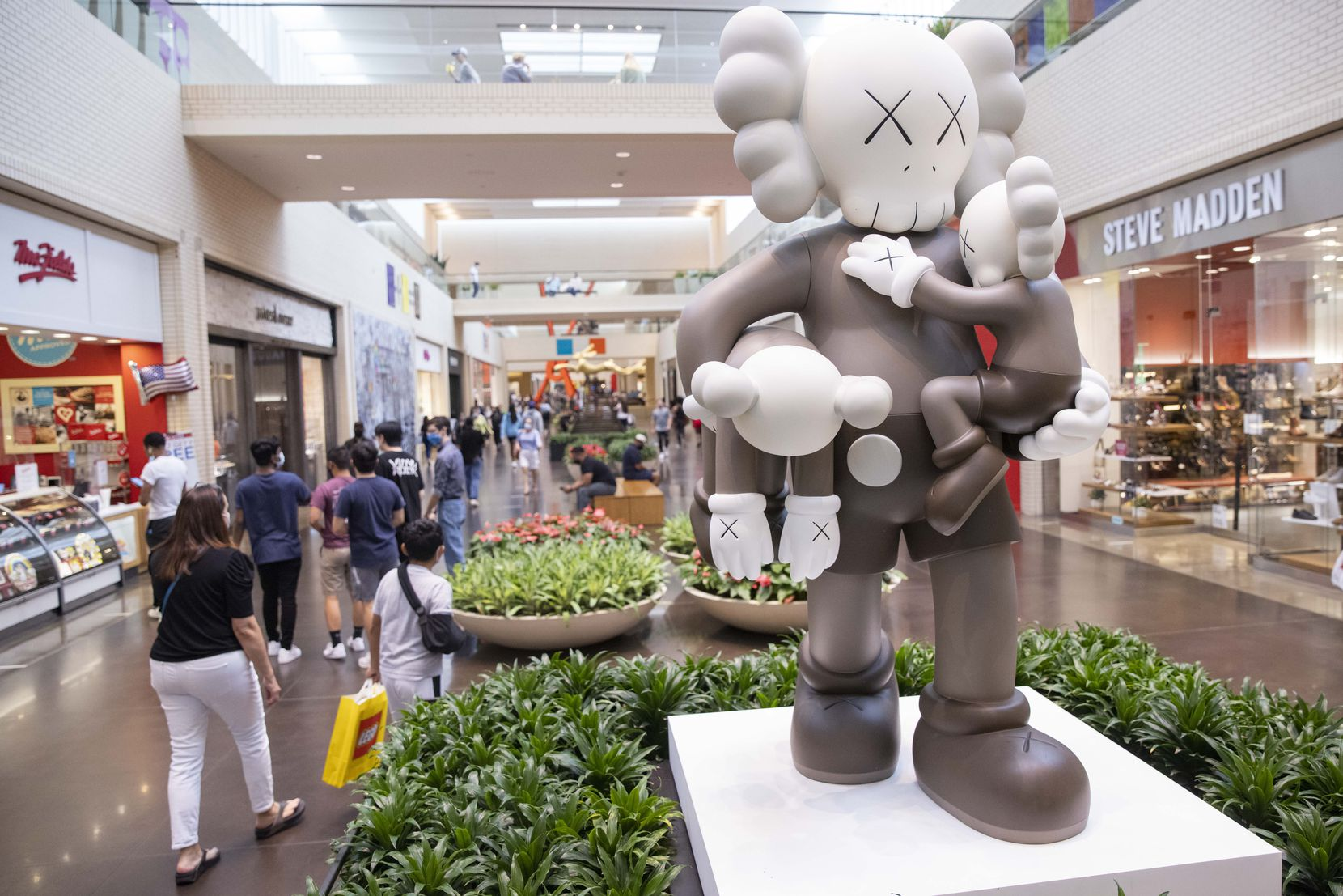 """Shoppers walk by KAWS' """"CLEAN SLATE"""" at NorthPark Center. The mall is trying to help both job seekers and stores with job openings."""