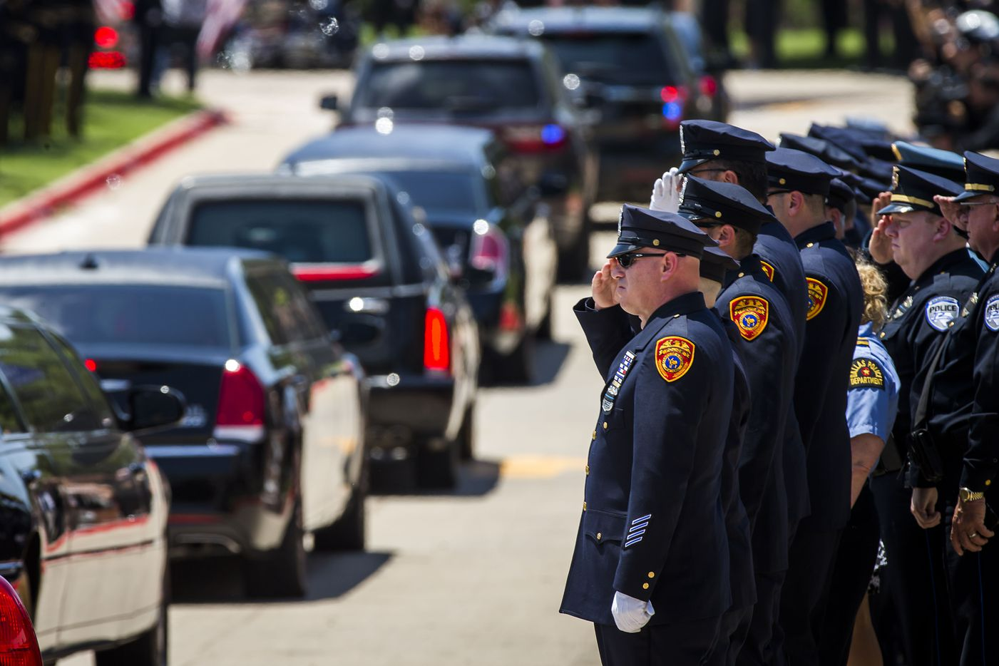 Law enforcement officer salute as the hearse carrying Dallas police Sr. Cpl. Lorne Ahrens departs Prestonwood Baptist Church following funeral services on Wednesday, July 13, 2016, in Plano.