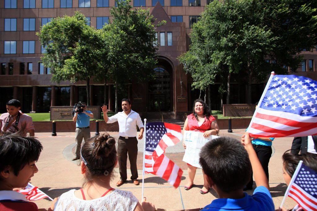 Ramiro Luna, left,  and Greisa Martinez, immigrant leaders,  lead chants outside the office of Sen. John Cornyn on June 12, 2013.