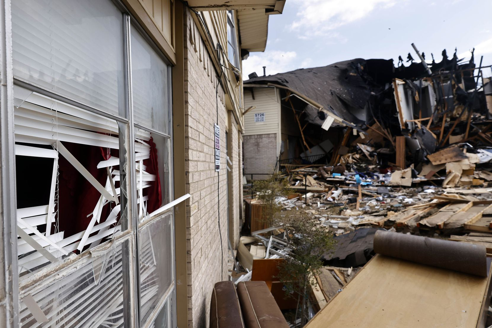 Exterior windows are visible in a nearby building following the explosion of a flat in the 5700 block of Highland Hills Drive.
