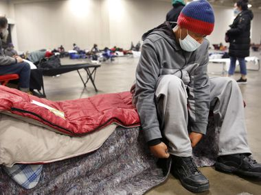 Pierre Scott, a 59 year-old guest and volunteer at a warming center run by OurCalling, changed socks on his cot at the Kay Bailey Hutchison Convention Center in Dallas, Tuesday, Feb. 16, 2021. Scott like a lot of other folks, found refuge from the overnight sub-zero temperatures. (Tom Fox/The Dallas Morning News)