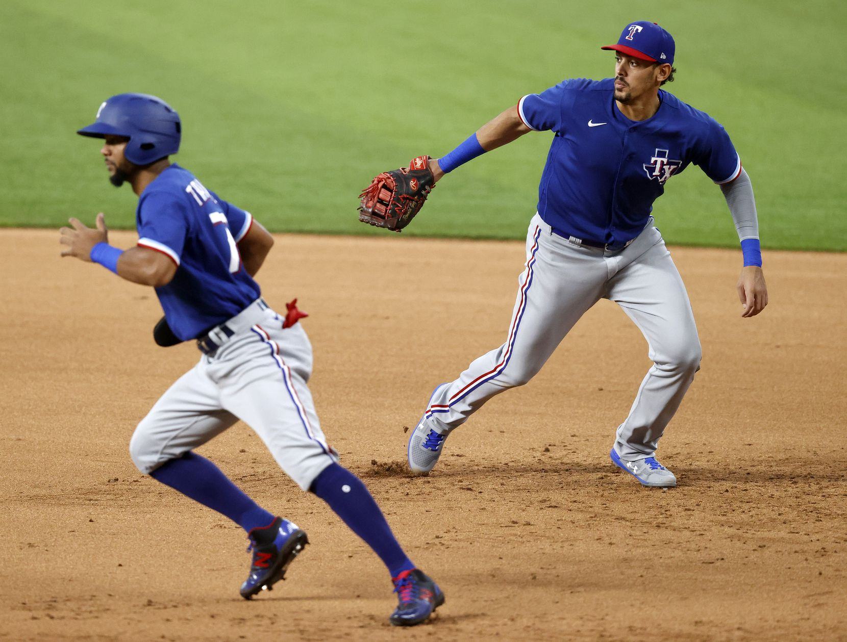 Texas Rangers first baseman Ronald Guzman (right) breaks for the base on an infield hit as Leody Taveras runs to second during an intrasquad game at Summer Camp inside Globe Life Field in Arlington, Texas, Friday, July 10, 2020. (Tom Fox/The Dallas Morning News)
