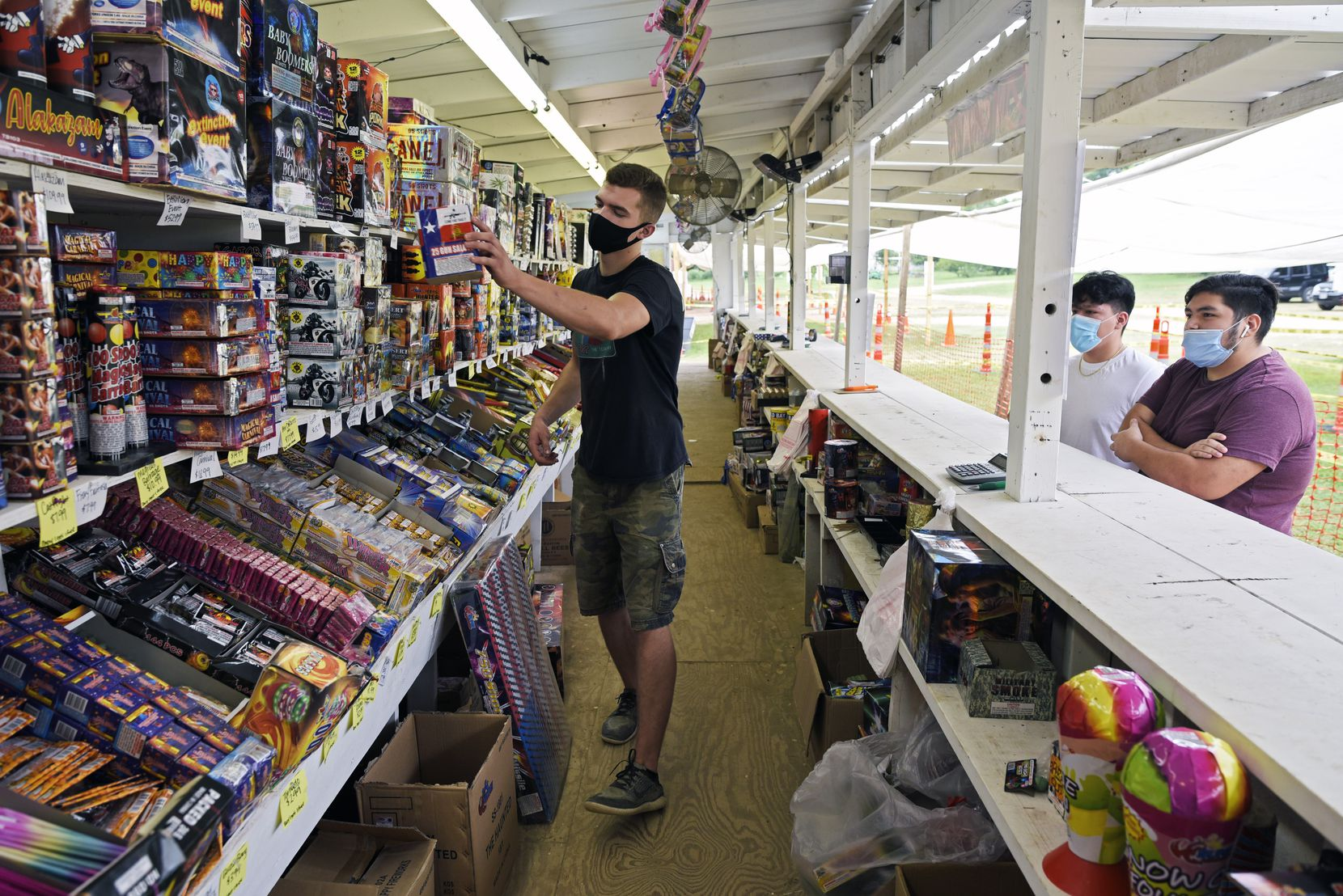Colton Lusk helped Cristian Lopez and Jose Cervera (far right), both 17, make selections at Palmer Fireworks in Dallas on Tuesday.