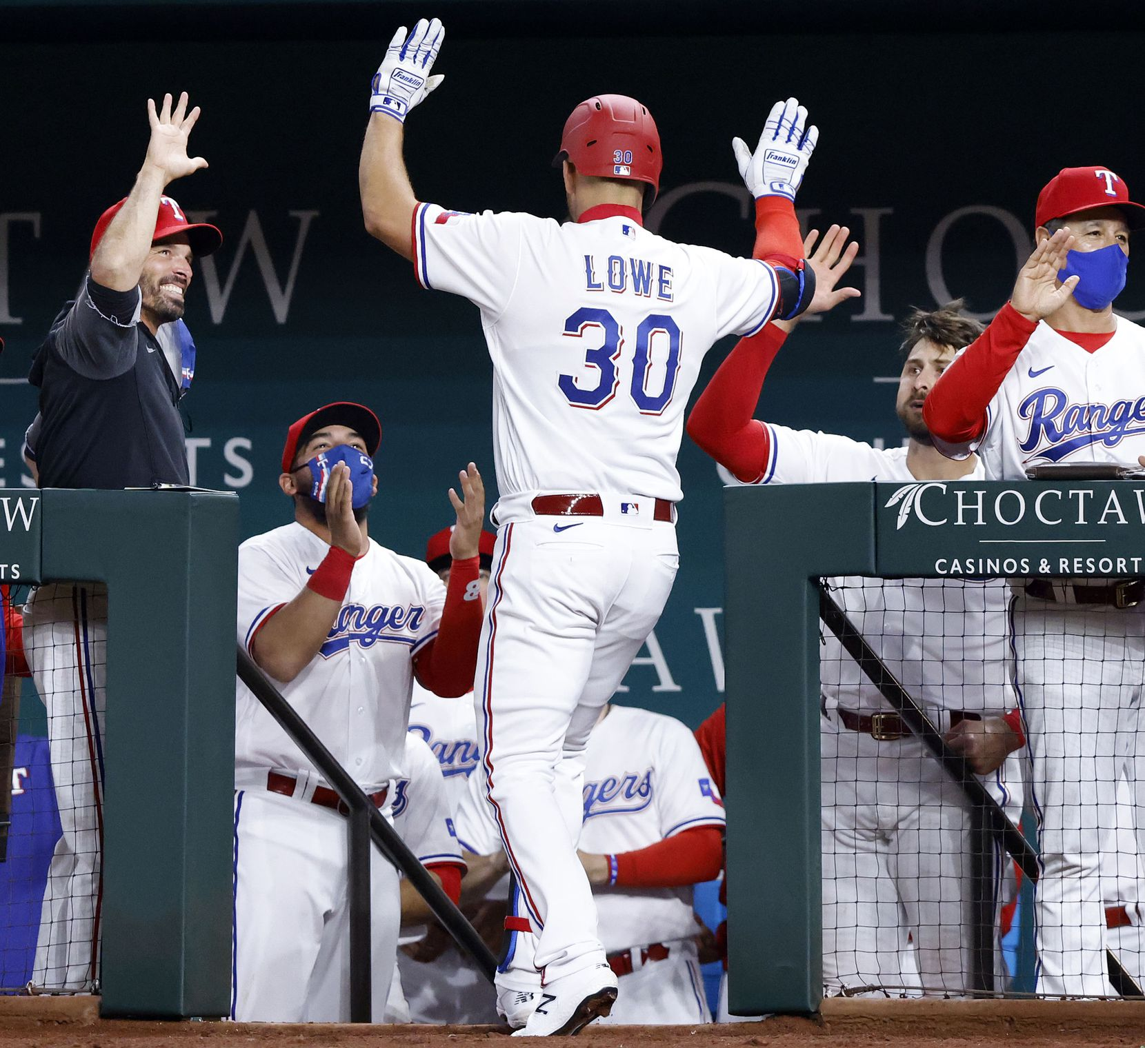 Texas Rangers batter Nate Lowe is congratulated by manager Chris Woodward (left) and teammate Joey Gallo (right) after connecting on a two-run homer during third inning against the Toronto Blue Jays at Globe Life Field in Arlington, Tuesday, April 7, 2021. Lowe scored David Dahl (21). (Tom Fox/The Dallas Morning News)