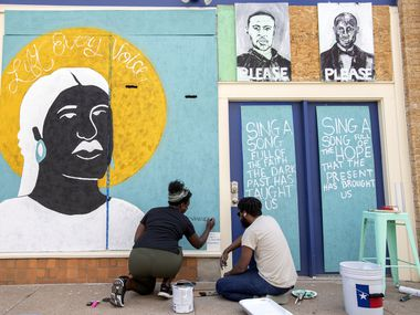 Desiree Vaniecia and Joeneal Berry sign their names on a mural they painted on plywood on Monday, June 1, 2020 in Deep Ellum in Dallas.