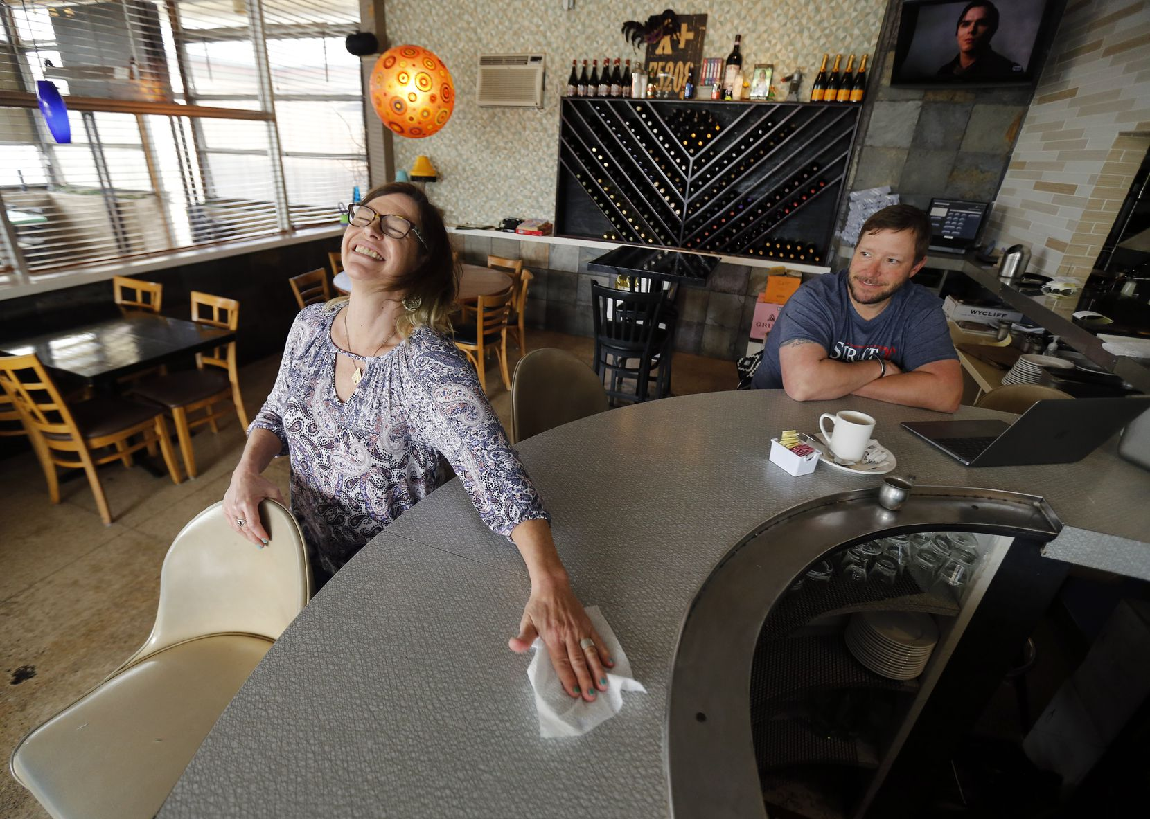 With the music playing, Kari Lynn Scott (left) playfully disinfected the bar on Saturday, March 21, as she and owner Matthew Yates waited for their regulars to stop by at Nova, a popular Oak Cliff neighborhood restaurant and bar that's had to close for sit-down service because of the coronavirus. (Tom Fox/The Dallas Morning News)
