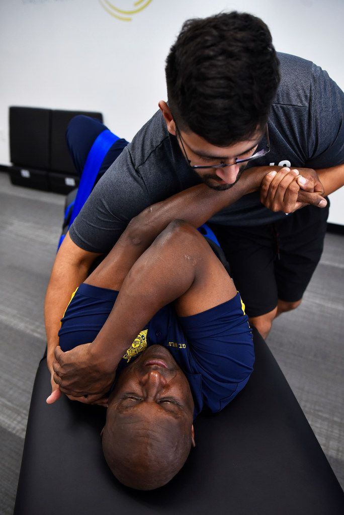 Stretch practitioner Shan Hussain works on client Sergeant Nathan Wilson, of the Dallas County Sheriff Department, as Hussain pushes and pulls Wilson's limbs during a session at Stretch Zone in Dallas.