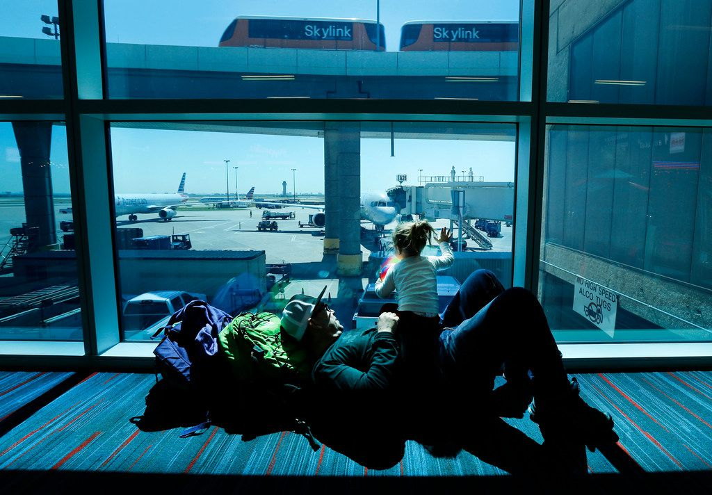 Enrique Ordonez of Aspen, Colo., played with his 2-year-old daughter, Valentina, in the shaded sunlight of Terminal A at DFW International Airport on April 16, 2018. DFW Airport is testing new window technology that varies the opacity of dynamic glass panes to let in less light, making seating areas cooler and more comfortable while also cutting cooling costs. One of the gates in Terminal A and a burger joint have the electrically charged blue-tinted windows installed. (Tom Fox/The Dallas Morning News)