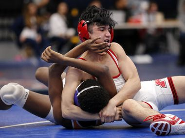 Allen High wrestler Kade Moore (top) gains control of Rockwall's Zach Flowers during their 120-pound championship match at the Region II 6-A Wrestling Championships in Allen, Texas, Saturday, February 15, 2020. Moore defeated Flowers.