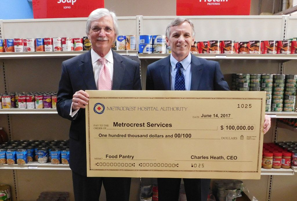 Charles Heath (left), CEO of Metrocrest Hospital Authority, delivered a $100,000 check to Tracy Eubanks, CEO of Metrocrest Services, at its food pantry earlier this year. The hospital authority agreed to give Metrocrest Services up to $100,000 if it raised additional funds through a match campaign.