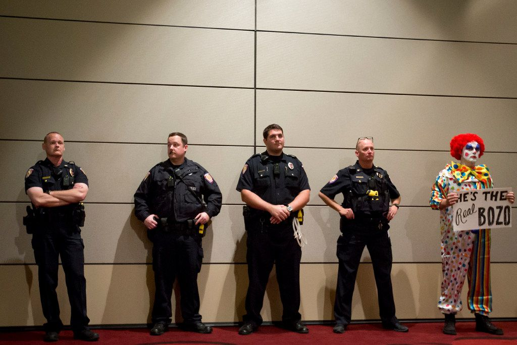 A protester stands along a wall with police as Richard Spencer speaks at the Memorial Student Center at Texas A&M University on Dec. 6, 2016.