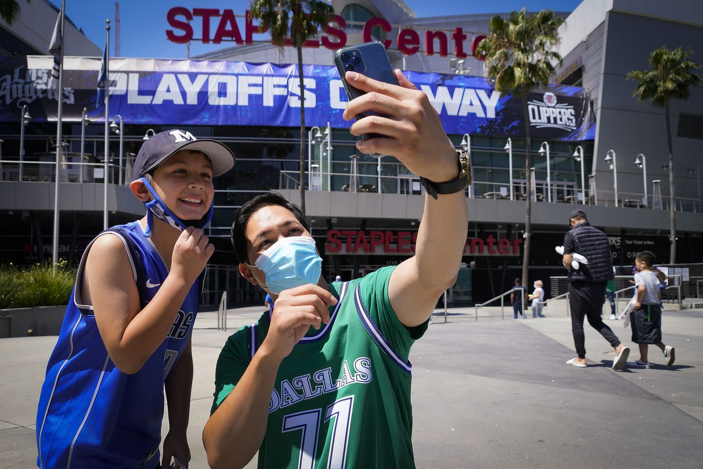 Dallas Mavericks fan Michael Chen and his son Jack, 8, take a selfie outside the arena before Game 7 of an NBA playoff basketball series against the LA Clippers at the Staples Center on Sunday, June 6, 2021, in Los Angeles.