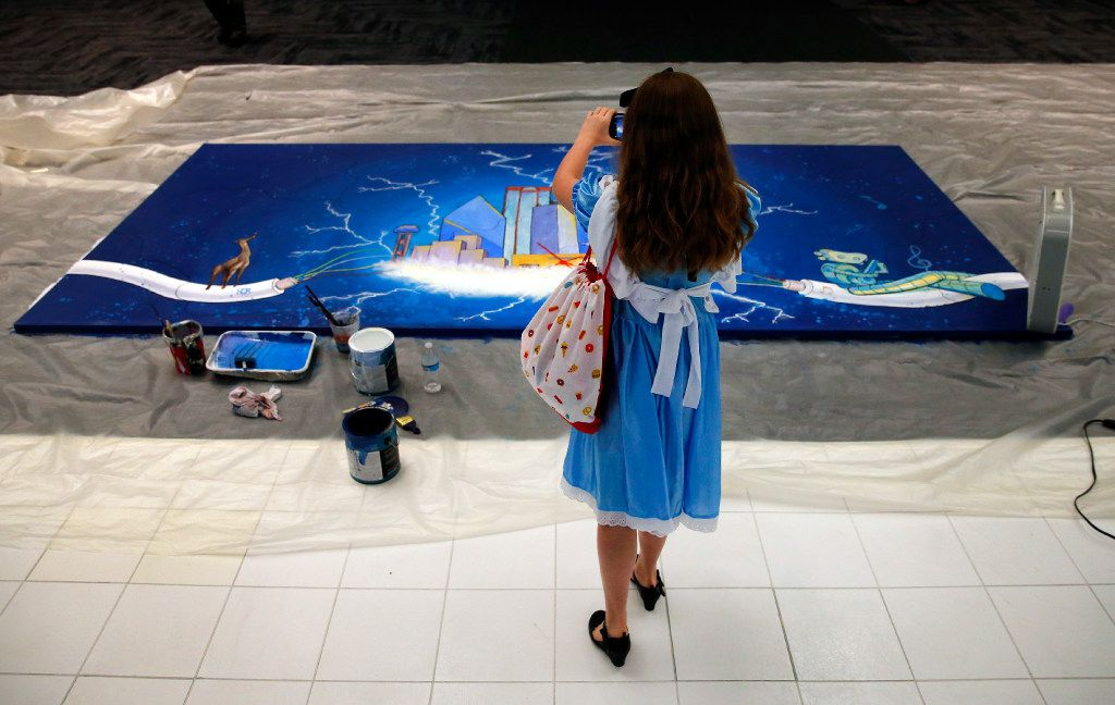 Ten-year-old Grace Henington, dressed as Alice in Wonderland, takes a picture of a painting of the Dallas skyline, part of a daylong project by artists at the Dallas Festival of Ideas . (Tom Fox/Staff Photographer)