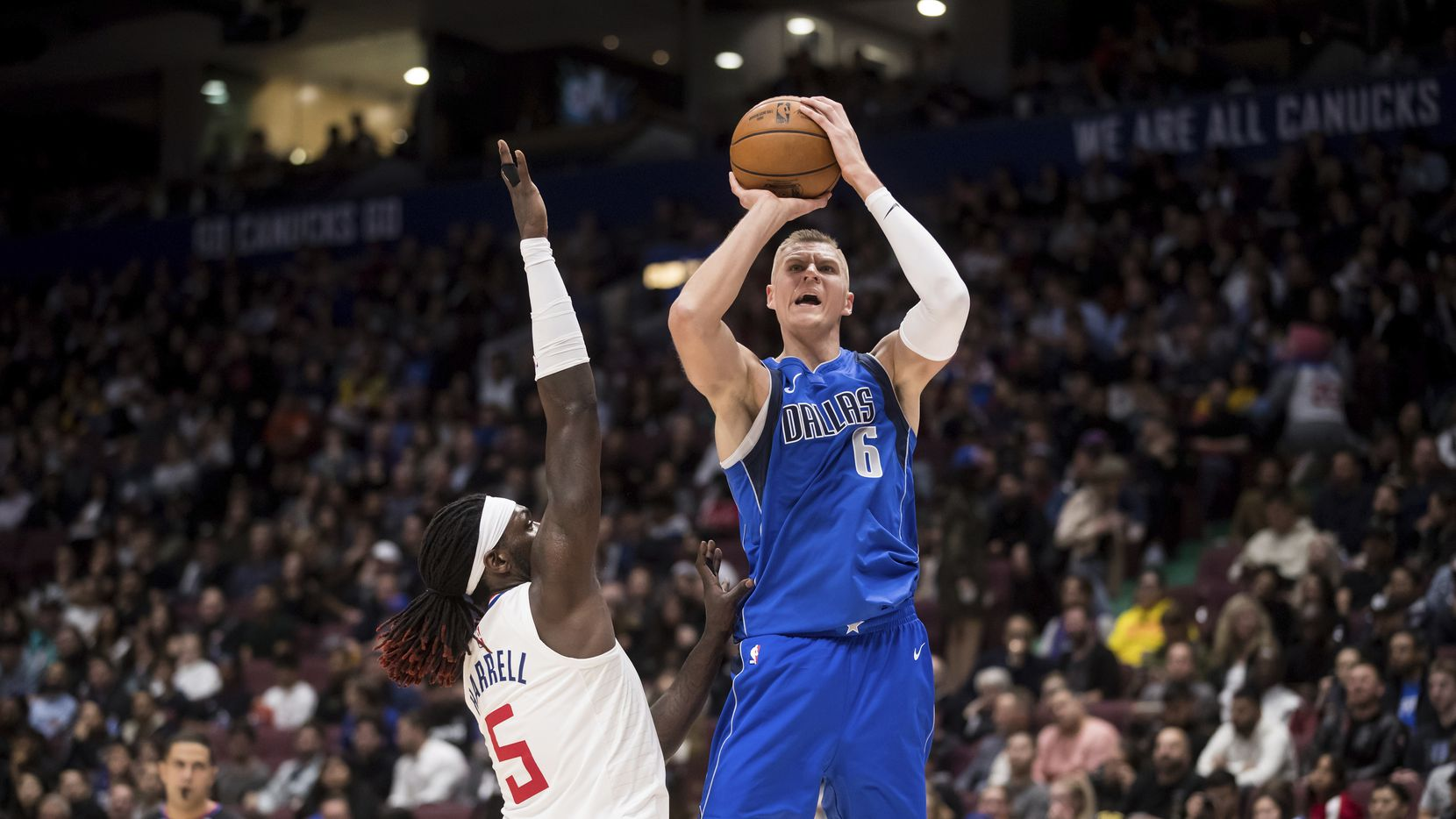 Kristaps Porzingis (6) of the Mavericks shoots over Los Angeles Clippers' Montrezl Harrell (5) during the second half of an NBA preseason basketball game Thursday, Oct. 17, 2019, in Vancouver, British Columbia.