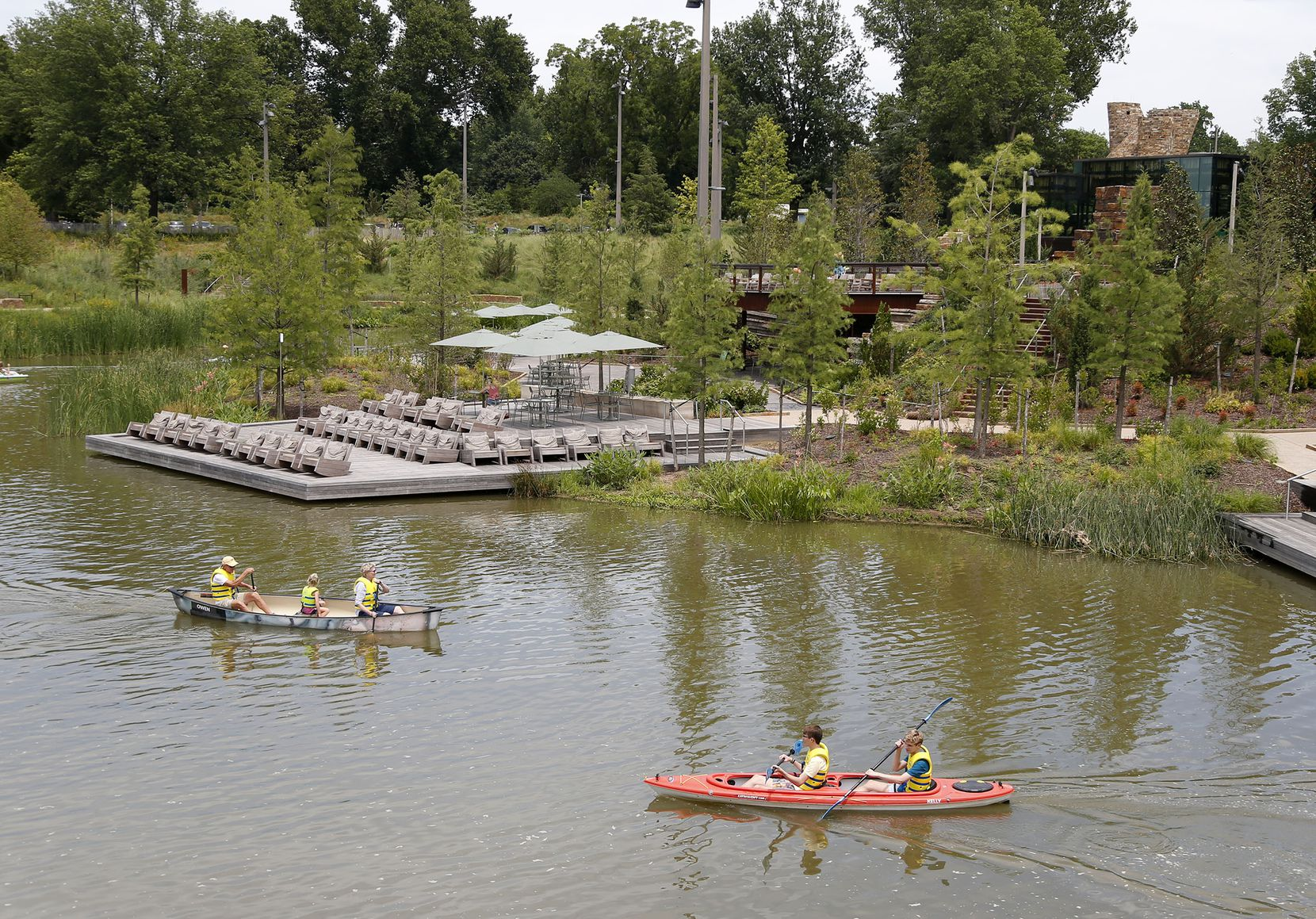 """Boaters paddled on Peggy Pond at Gathering Place in Tulsa in July 2019. New Dallas Park Conservancy president and CEO Tony Moore said, """"It had to take something very, very compelling for me to leave an awesome park"""" like the one he led in Tulsa."""