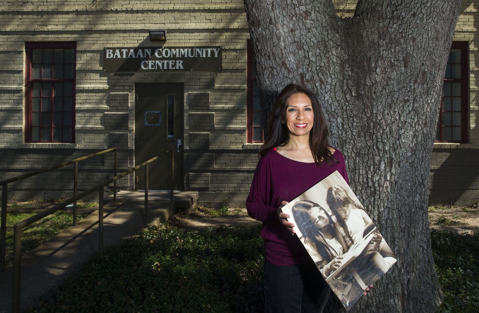 Maria Lozada Garcia, La Bajada Neighborhood Community Association president, poses for a portrait at the Bataan Community Center in Dallas on Monday, February 25, 2019. She holds a photograph of herself (right) when she was in preschool, learning to read at the community center.