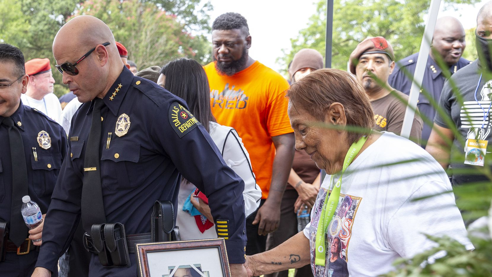 Dallas Police Chief Eddie Garcia (left) escorts Bessie Rodriguez, mother of Santos Rodriguez, back to her seat after placing a wreath on her son's headstone during a memorial service at Oakland Cemetery in South Dallas on Saturday, July 24, 2021.