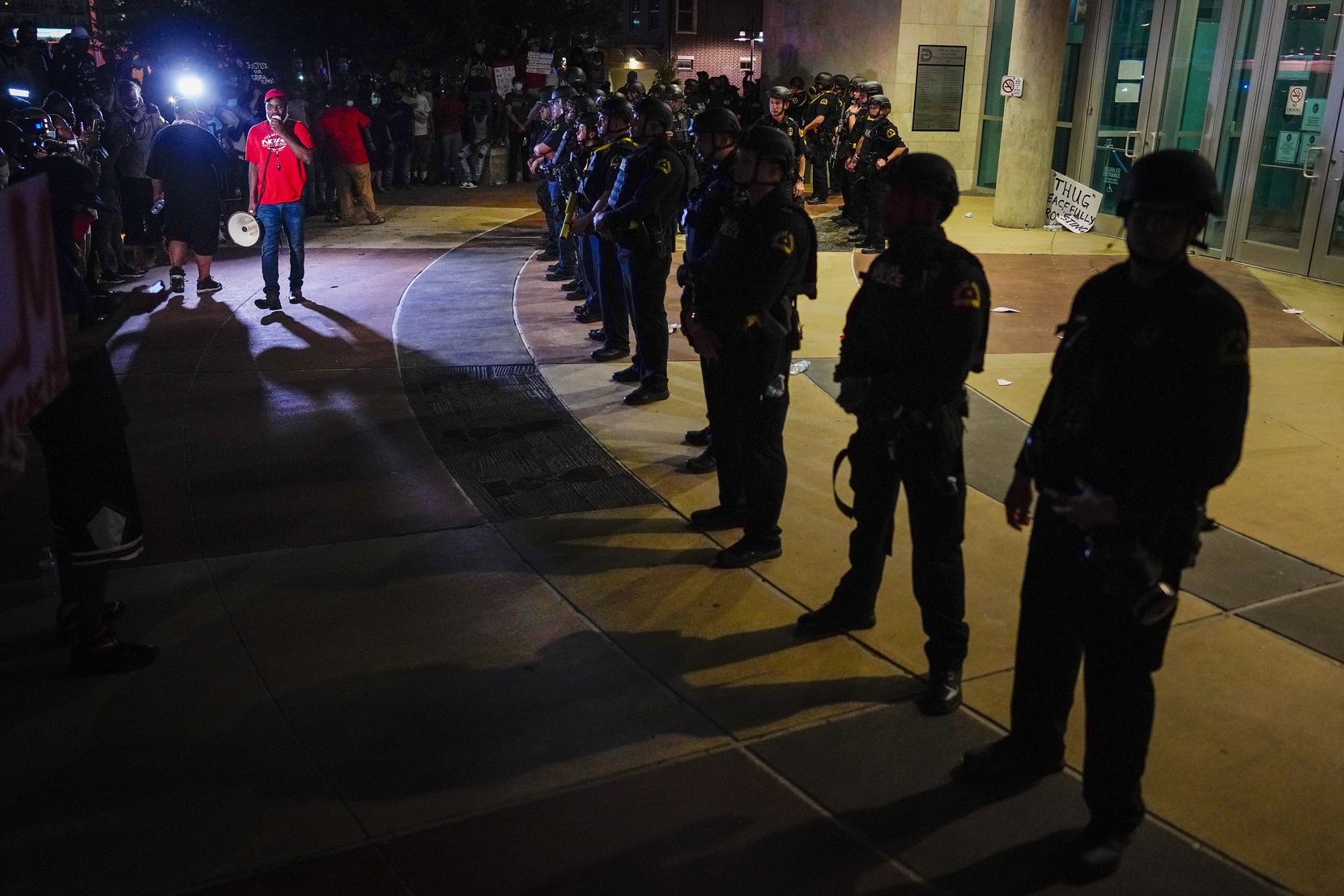 Dallas police form a line outside the front door of the the Dallas Police Headquarters as Dominique Alexander, the head of Next Generation Action Network, addresses a protest against police brutality on Friday, May 29, 2020, in Dallas.