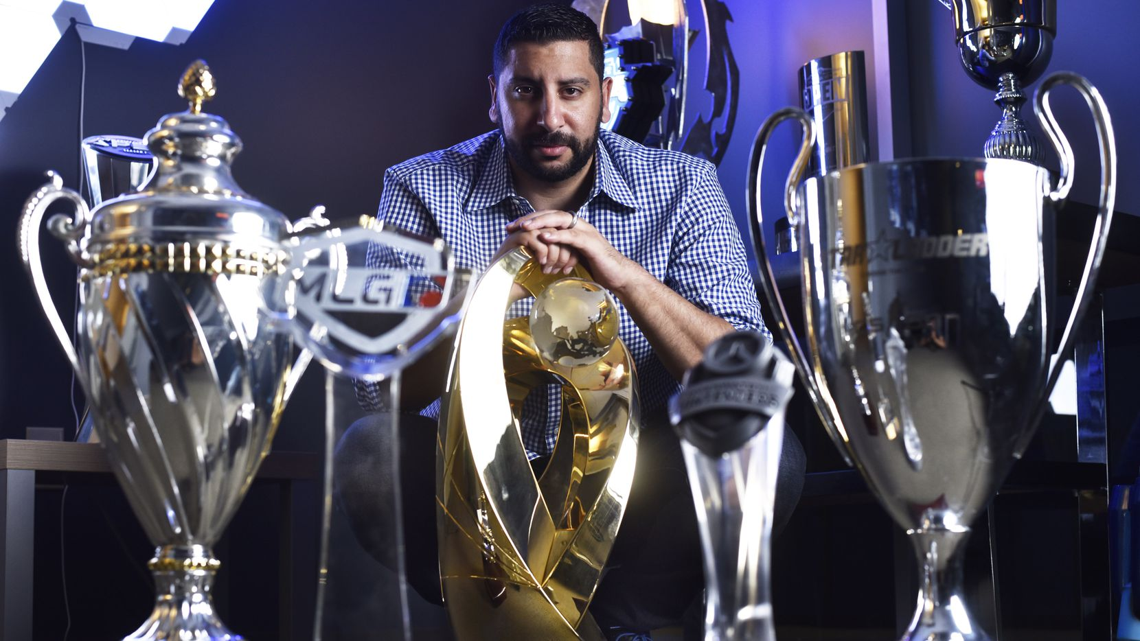 Mike Rufail, chief executive officer and owner of Envy Gaming and the Dallas Fuel, poses with with several esports championship trophies at their offices in Dallas in August.. The trophy in the middle is from the 2016 World Electronic Sports Games in China for the CS:GO team.