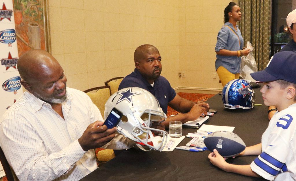 Former Dallas Cowboys running back Emmitt Smith scans a helmet after signing it for a fan at a GameDay Sports Tours dinner in 2016. He added the step after growing frustrated with counterfeit sports memorabilia.