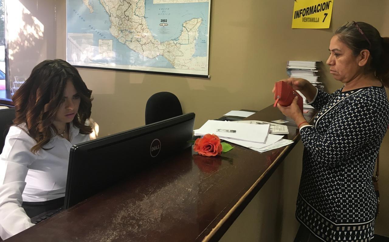 Linda Lozado, la encargada de la ventanilla de Banjército dentro del Consulado General de México en Dallas, ayuda a una cliente a adquirir su permiso de vehículo. (AL DÍA/KARINA RAMÍREZ)