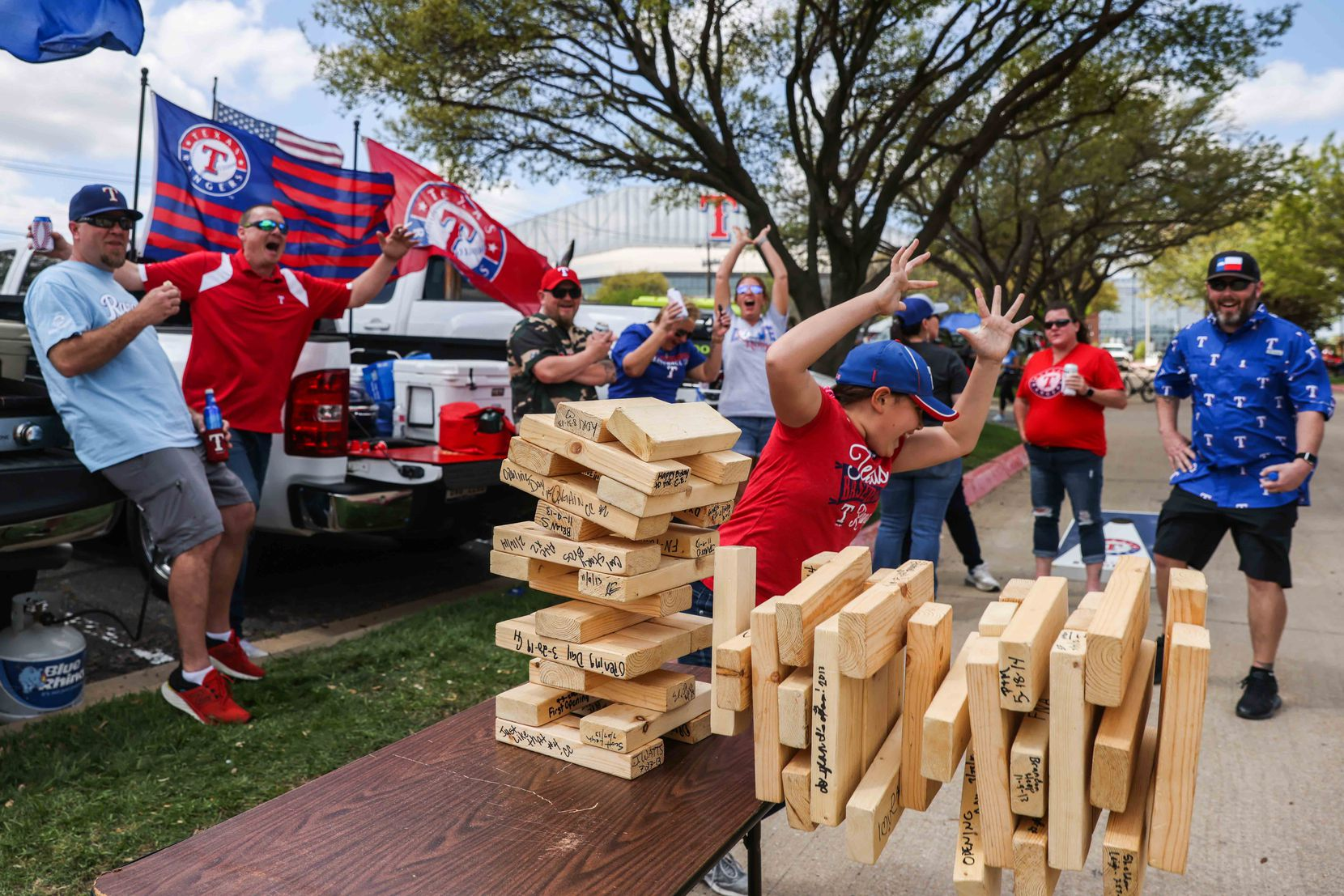 Sylar Watts, 11, reacts along with people around  as the Jenga tower falls during a gathering outside the Globe Life Field before the game between Texas Rangers and Toronto Blue Jays on opening day in Arlington, Texas on Monday, April 5, 2021. (Lola Gomez/The Dallas Morning News)