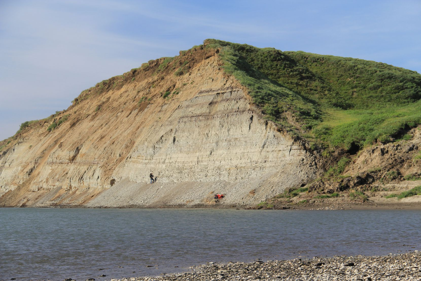 Dr. Paul McCarthy standing at the base of the bluff along Alaska's Colville River in 2012 where the baby dinosaur's jawbone was found.