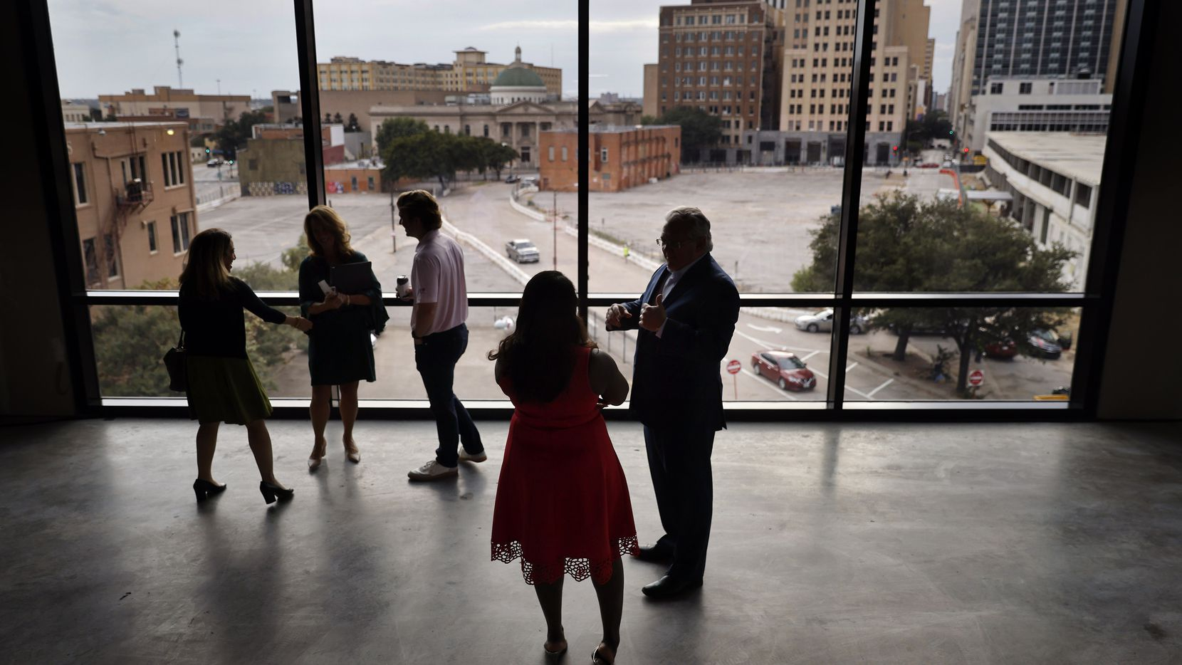 """Guests at the ceremonial """"groundbreaking"""" of Harwood Park, the last of four spaces that Parks for Downtown Dallas committed to building, look out over the concrete parking lots that will be transformed into greenspace."""