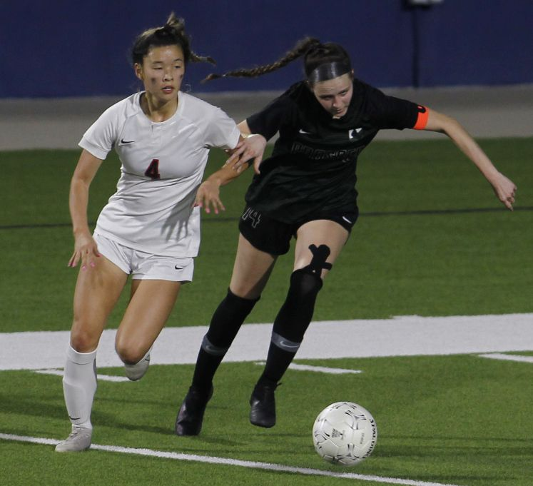 Prosper's Lauren Holland (14), right, and Coppell's Michelle Pak (4) battle for ball possession during first half action. Prosper prevailed, 2-0 to advance. The two teams played their Class 6A bi-district girls soccer playoff game at McKinney ISD Stadium in McKinney on March 26, 2021. (Steve Hamm/ Special Contributor)