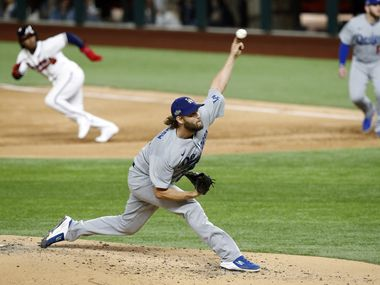 As Atlanta Braves Ozzie Albies (1) breaks for second base, Los Angeles Dodgers starting pitcher Clayton Kershaw (22) throws a pitch during the second inning in Game 4 of the National League Championship Series at Globe Life Field in Arlington, Thursday, October 15, 2020.