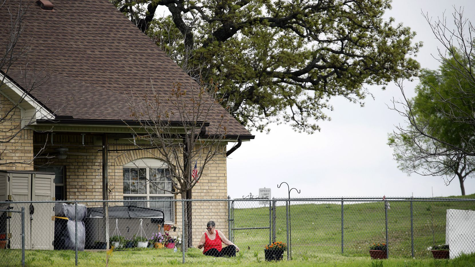 A woman pulls weeds in her yard outside one of the cottage duplex units at Texas Masonic Retirement Center on W. Division St. in Arlington on Wednesday March 18, 2020.