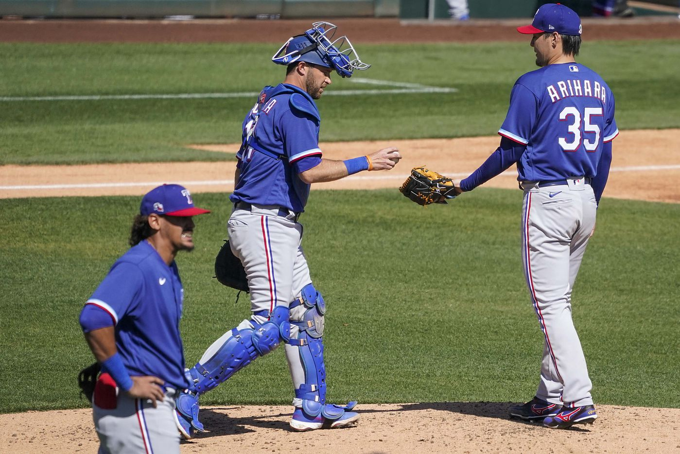 Texas Rangers pitcher Kohei Arihara (35) gets a visit from catcher Drew Butera  after giving up a single to load the bases during the second inning of a spring training game against the Chicago White Sox at Camelback Ranch on Tuesday, March 2, 2021, in Phoenix, Ariz.