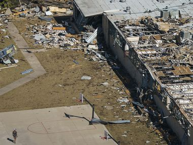 A man walks on a basketball court at Thomas Jefferson High School in an aerial view of tornado damage on Monday, Oct. 21, 2019, in Dallas. (Smiley N. Pool/The Dallas Morning News)