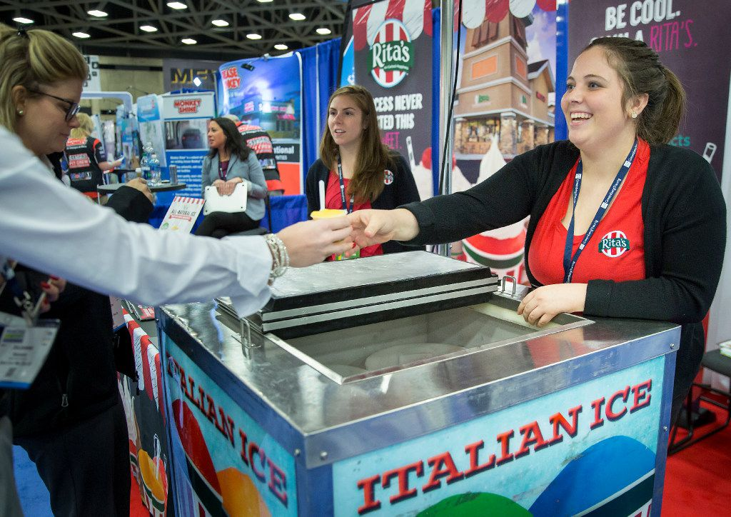 Emily Lewis hands a sample of mango ice to a visitor to the Rita's Italian Ice booth at Franchise Expo South Kay Bailey Hutchison Convention Center in Dallas. (Smiley N. Pool/The Dallas Morning News)
