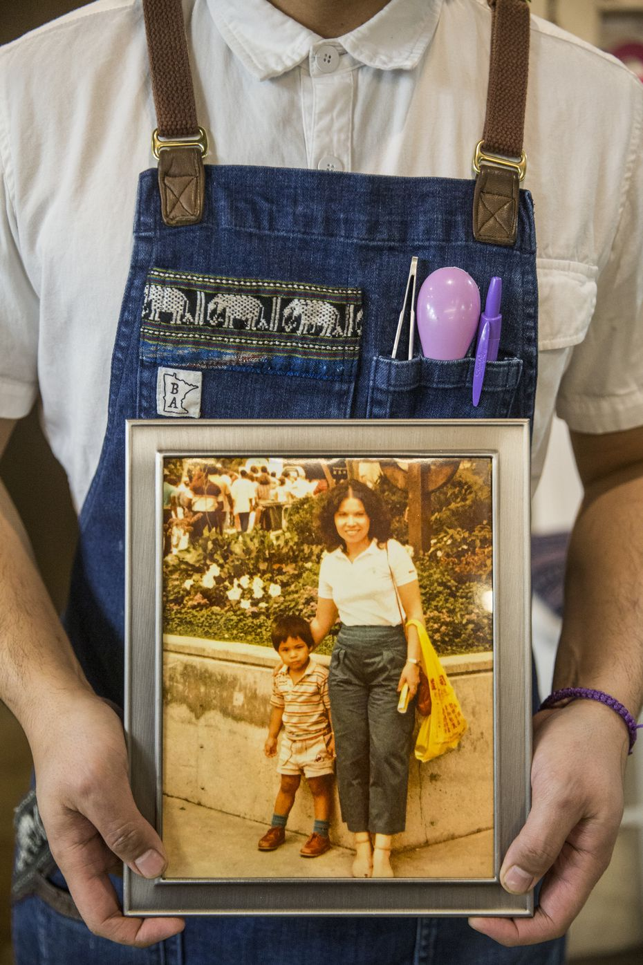 Chef Donny Sirisavath holds a photo of he and his mother Phaysane Sirisavath, who died of cancer. Sirisavath's restaurants Khao Noodle Shop and Khao Gang are inspired by her cooking.