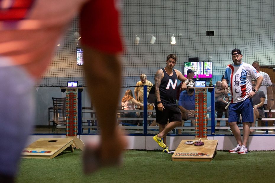 Cody Hughes and Trey Sparks watch as Mac tosses a bag during a cornhole tournament hosted by North Texas Cornhole at the Blue Sky Sports Center in Allen, TX on July 1, 2021. North Texas Cornhole's event was a Switcholio Night, where players are randomly assigned new partners for each round while being ranked on an individual basis.
