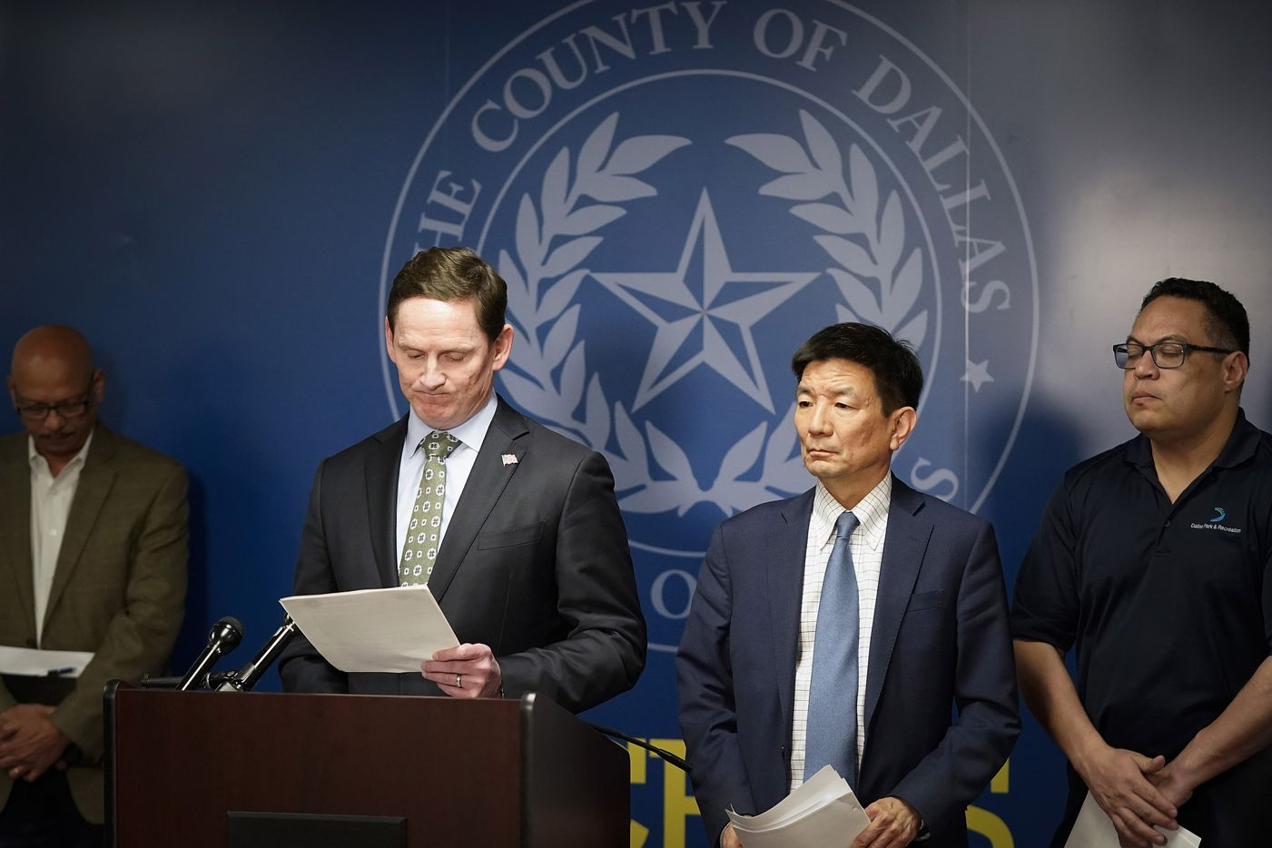 Dallas County Judge Clay Jenkins announces that a local state of disaster for public health emergency has been declared in the county, due to more cases of the new coronavirus, late Thursday, March 12. 2020, in Dallas. To his right is Dr. Philip Huang, Director of Dallas County Health and Human Services. At far right is Dallas city council member Omar Narvaez.  At left is Rocky Vaz, City of Dallas Director of Emergency Management.