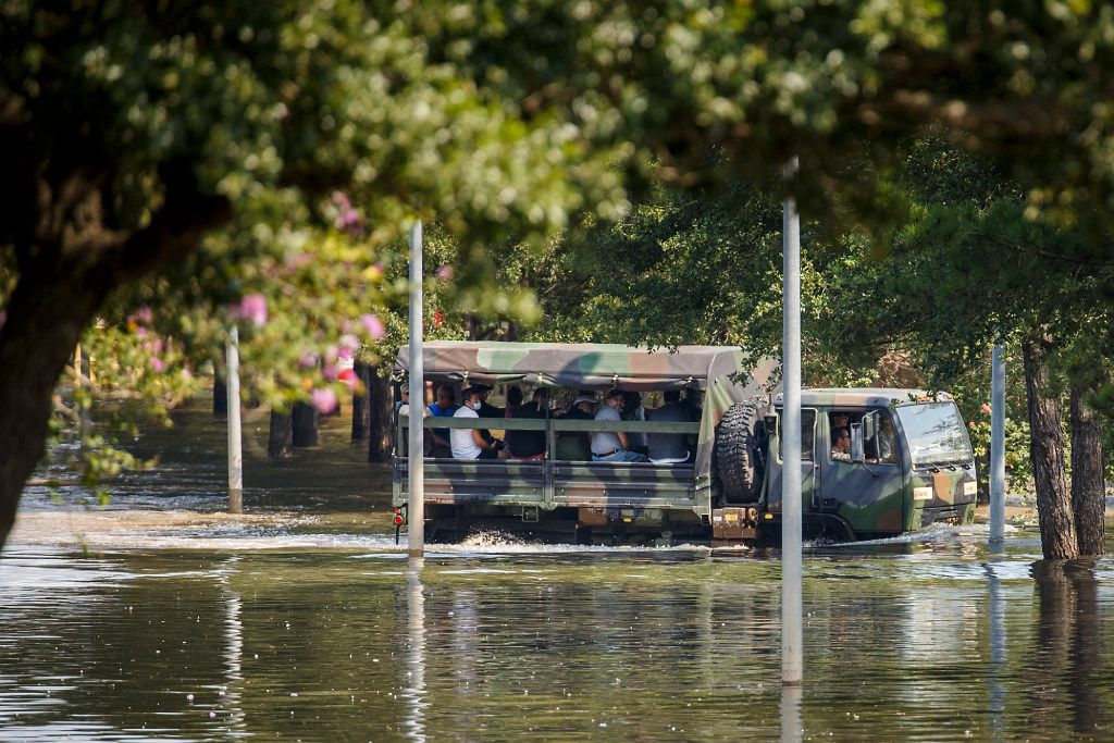 Residents ride in a military truck through flood waters left by Hurricane Harvey near the Cinco Ranch Canyon Gate subdivision on Saturday, Sept. 2, 2017.