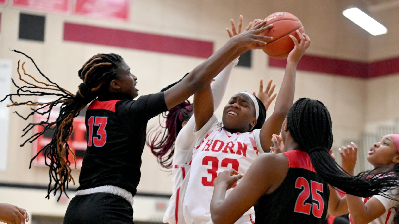 Horn's Vemell Atamah (32) grabs a rebound between Skyline's Jaida Mcdonald (13) and Breniya Arnold in the first half during a girls high school basketball game between Skyline and Mesquite Horn, Tuesday, Jan. 5, 2021, in Mesquite, Texas.