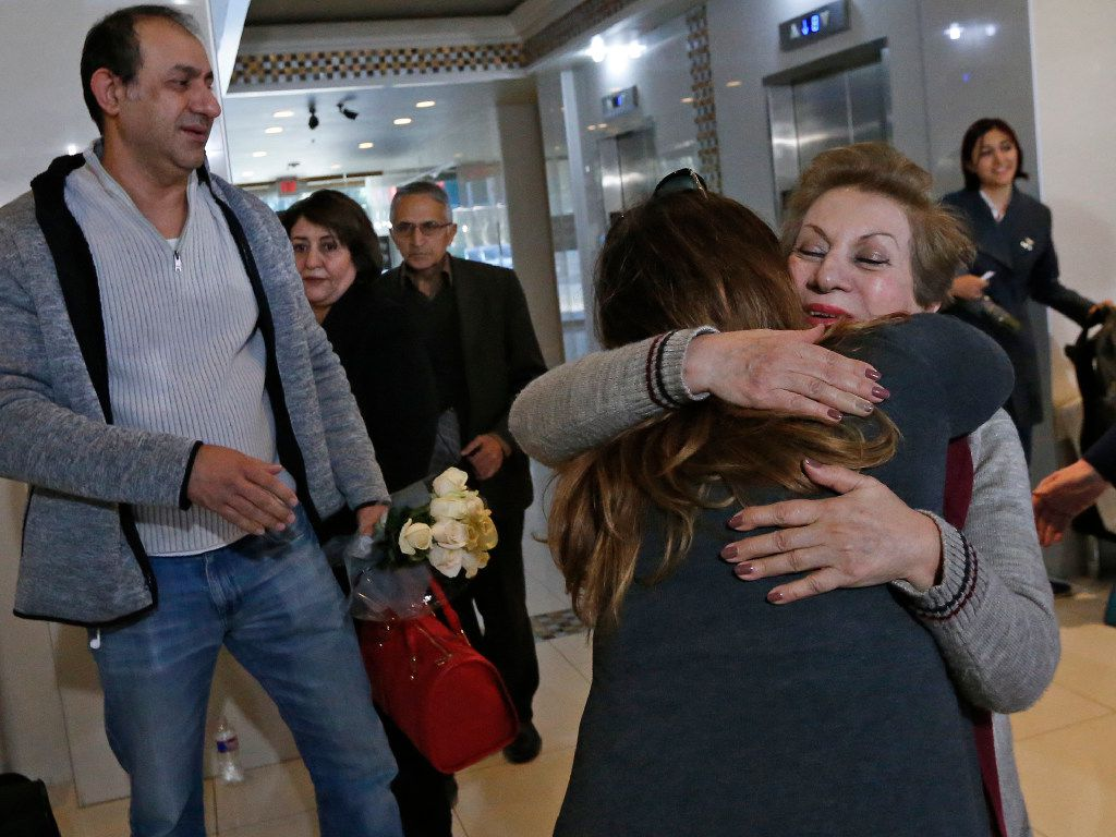 Shahin Hassanpour of Iran, facing camera, gets a hug from Anahita Basrami of Dallas after Hassanpour was released from detention at DFW Airport, as Behzad Honarjou, looks on after a media briefing in North Dallas  on Sunday, January 29, 2017. (Louis DeLuca/The Dallas Morning News)