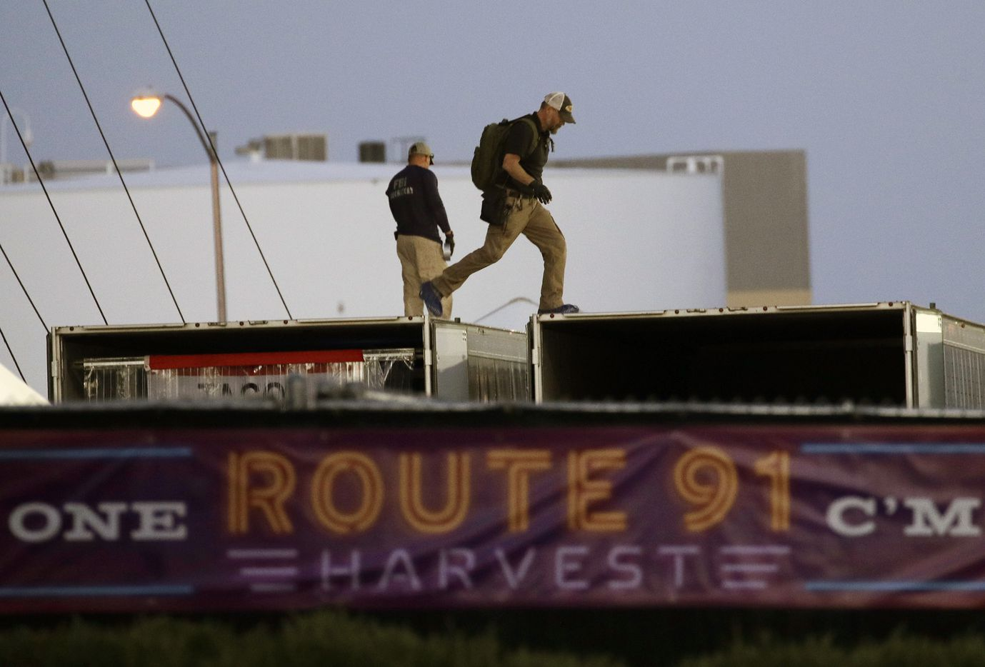FBI agents walk on the roof of boxes inside the concert grounds where a mass shooting occurred in Las Vegas, Tuesday, Oct. 3, 2017. Authorities are trying to determine why Stephen Paddock, a 64-year-old high-stakes gambler and retired accountant, killed dozens of people at Route 91 Harvest, a country music festival, Sunday in Las Vegas. (AP Photo/John Locher)