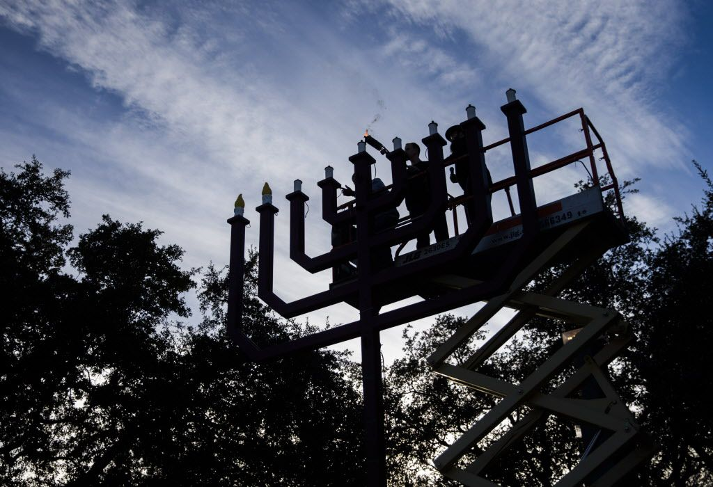 Evan Bundis, center, and Rabbi Moshe Naparstek, right, light the largest menorah in Texas on Thursday, December 29, 2016 at the Aaron Family Jewish Community Center of Dallas