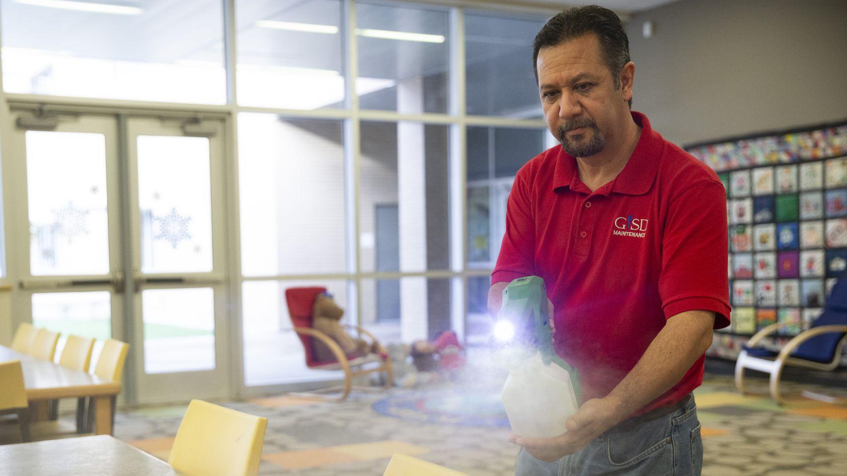 Raul Rodríguez desinfecta la Biblioteca de la primaria Daugherty en Garland.