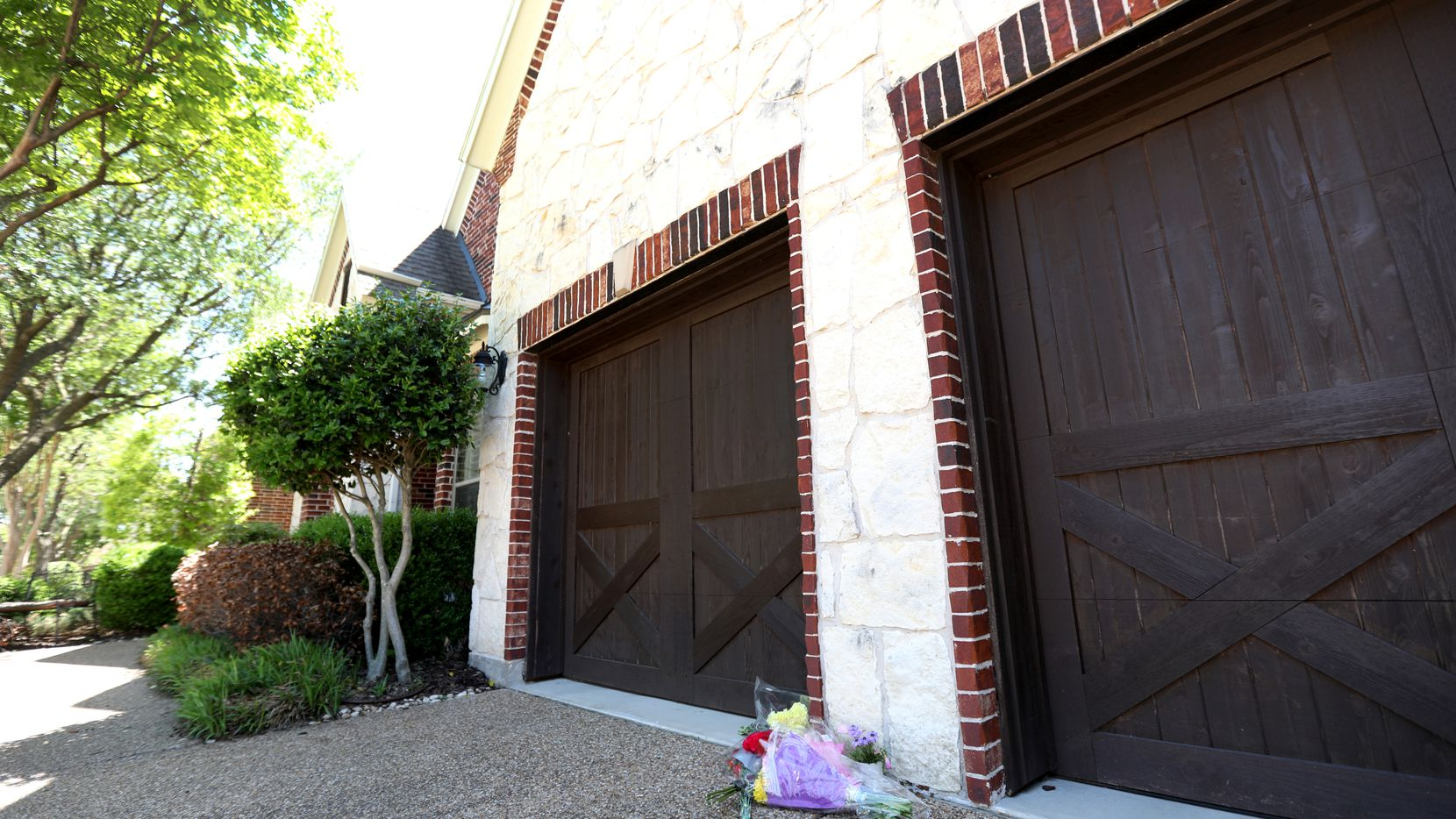 Flowers in front of the garage at 1847 Nueces Drive in Allen, Texas, Sunday, April 25, 2021. The home is where a 20-year-old man is believed to have killed his 51-year-old mother and 17-year-old sister.