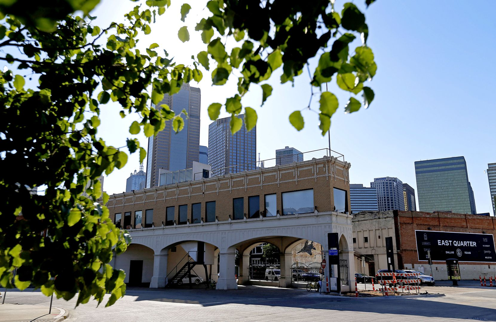 The original Magnolia Oil building (left), and a sign promoting the East Quarter redevelopment project are shown east of the downtown skyline as seen from South Cesar Chavez Boulevard in Dallas, Thursday, May 17, 2018.