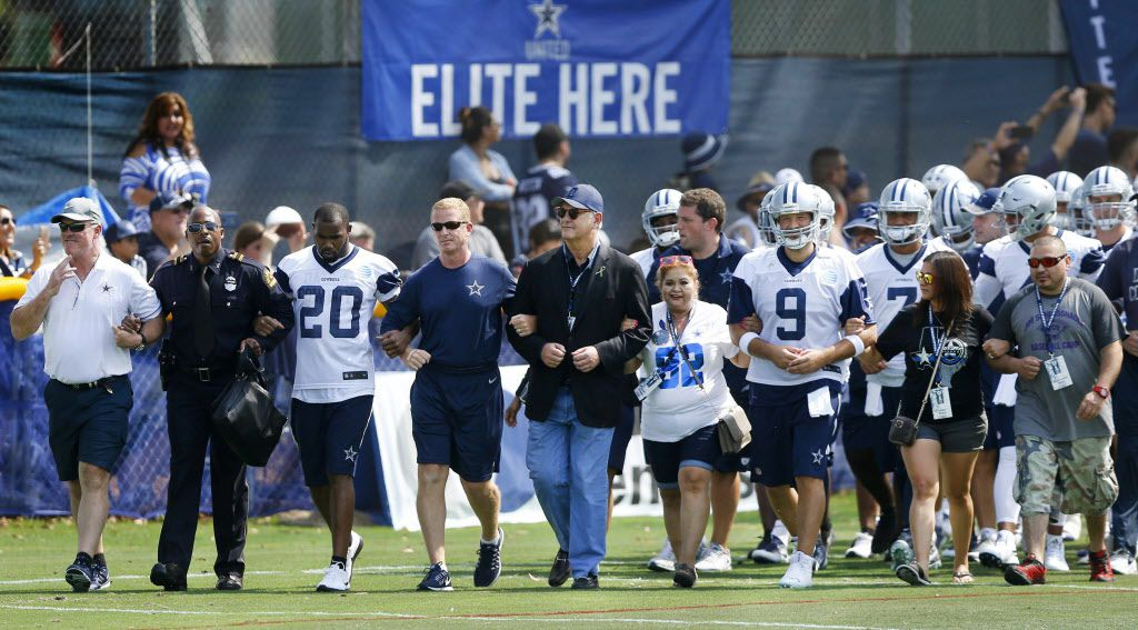 Dallas Mayor Mike Rawlings (center) walked arm-in-arm with Dallas Cowboys head coach Jason Garrett (to his right) along with players onto the field for the opening day of training camp in Oxnard, California, Saturday, July 30, 2016. Walking (from left) is Executive Vice President Stephen Jones, unknown Dallas office, Dallas Cowboys running back Darren McFadden (20), Garrett, Rawlings, Valerie Michelle Zamarripa, mother of slain Dallas offcier Patricio Zamarripa, quarterback Tony Romo (9), Laura Ann Sipolo, Patricio's sister and her husband Jessie Albert Reyes.  (Tom Fox/The Dallas Morning News)