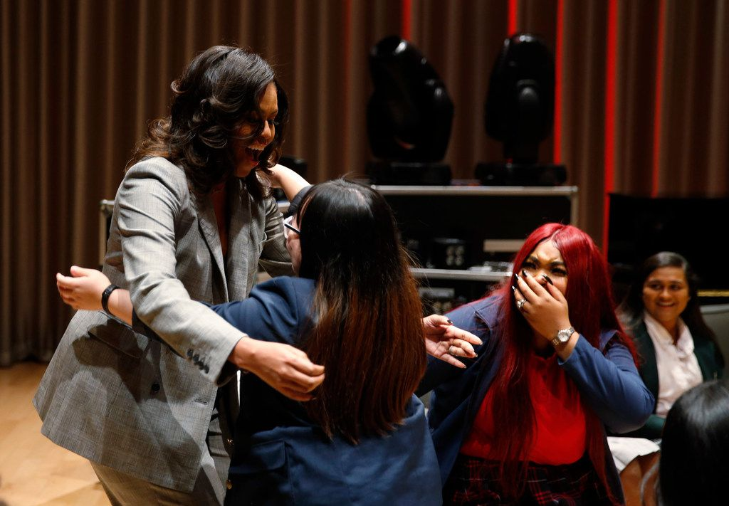 "Former first lady Michelle Obama hugs Htee Shee, 18 of Irma Lerma Rangel Young Women's Leadership School as Ashawnti Black, 18 (right) of Irma Lerma Rangel Young Women's Leadership School looks on after Obama surprised local high school students from Dallas during the first annual Young Women's Leadership Conference at Winspear Opera House in Dallas on Monday, December 17, 2018. Obama is in town promoting her book ""Becoming."" (Vernon Bryant/The Dallas Morning News)"