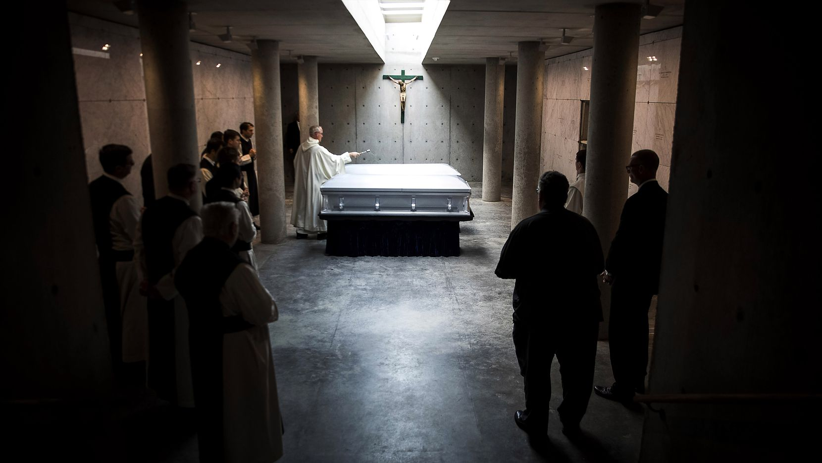 The Rev. Peter Verhalen, abbot of Cistercian Abbey Our Lady of Dallas, sprinkles holy water on the caskets of the Revs. Damian Szodenyi and Rudolph Zimanyi during their entombment service.